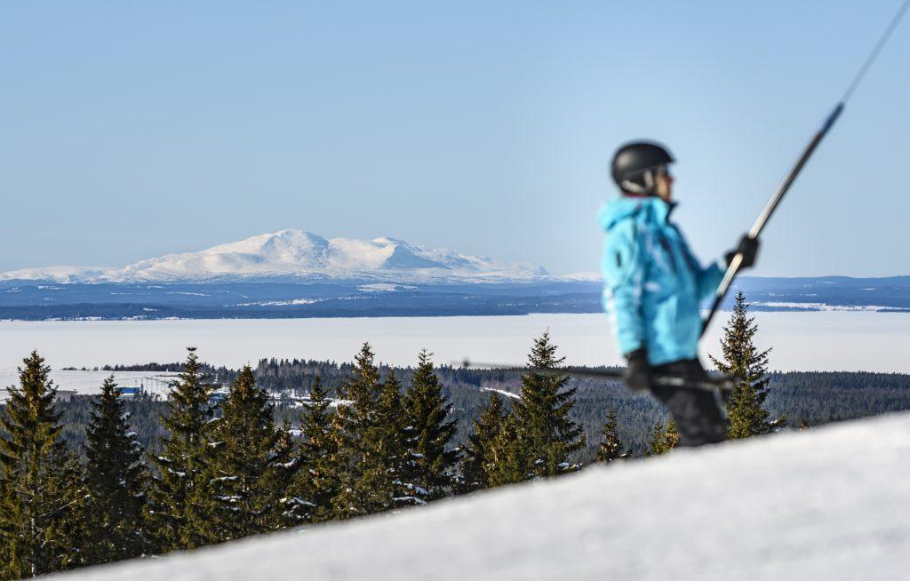 En slalomåkare åker upp för en slalombacke med liften. I bakgrunden syns gröna granar, istäckta Storsjön och snöiga fjäll. Foto Göran Strand.