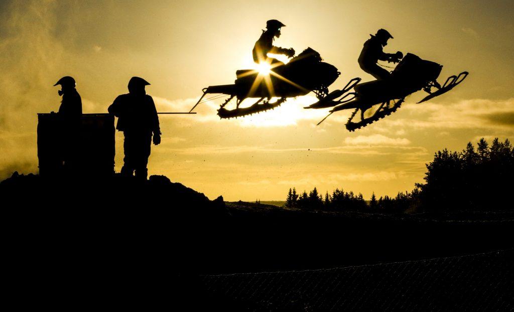 Siluetten av två snöskotrar som hoppar genom luften. Foto Roger Strandberg