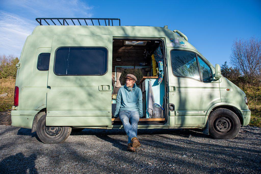 Person som sitter i öppningen av en minibuss. Foto: Jens Larsson