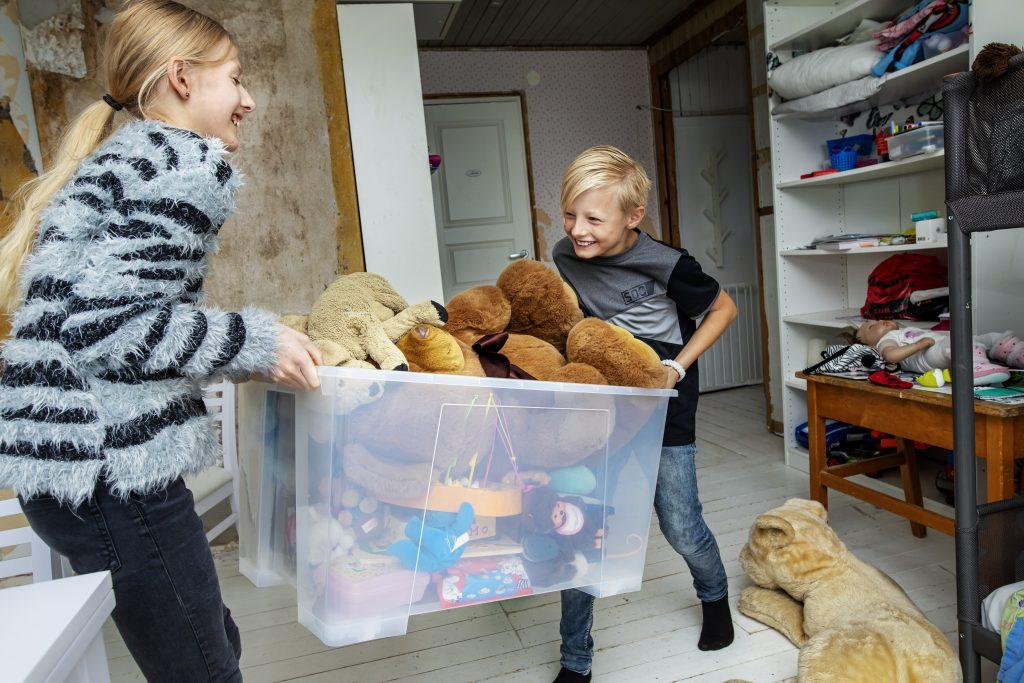 Två barn som lyfter en flyttlåda med leksaker Foto: Emelie Asplund