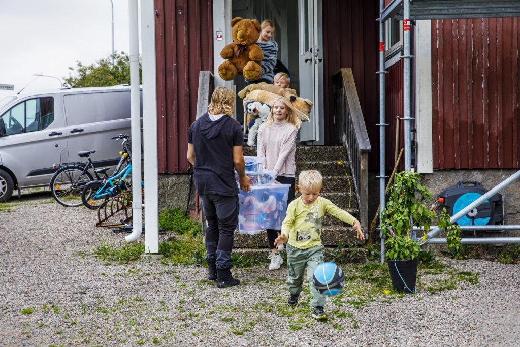 Familj som bär flyttlådor och gosedjur ut från ett hus. Foto: Emelie Asplund