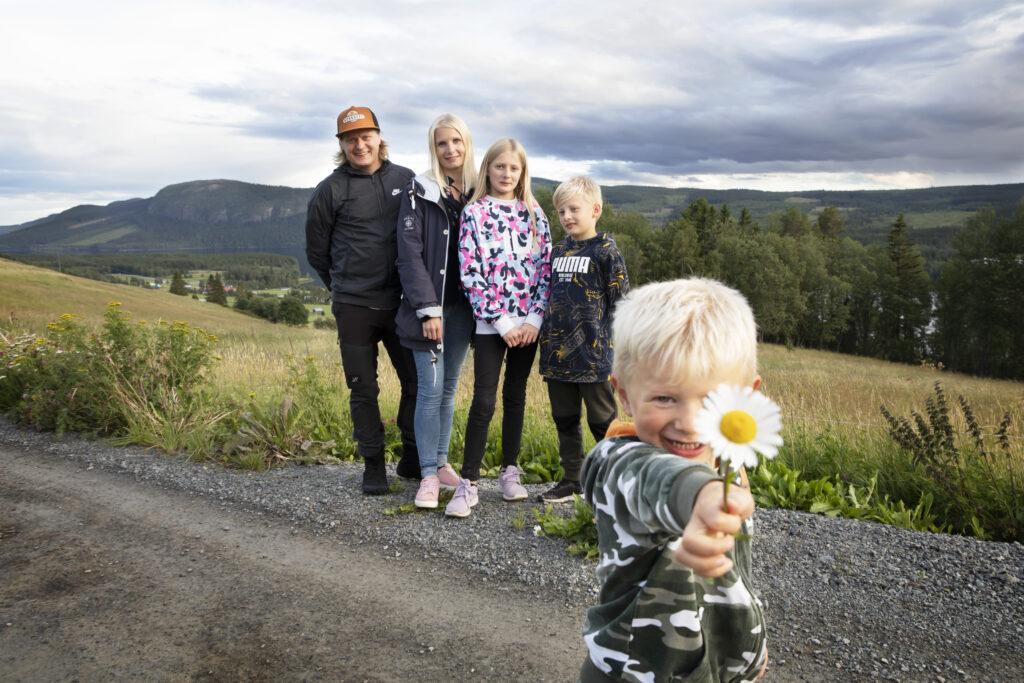 Familj som står framför ett berg där ett av barnen sträcker fram en prästkrage foto: Susanne Kvarnlöf