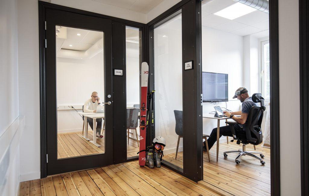 Två personer som jobbar på kontor, ett par slalomskidor står lutad mot en vägg. Foto Håkan Wike.