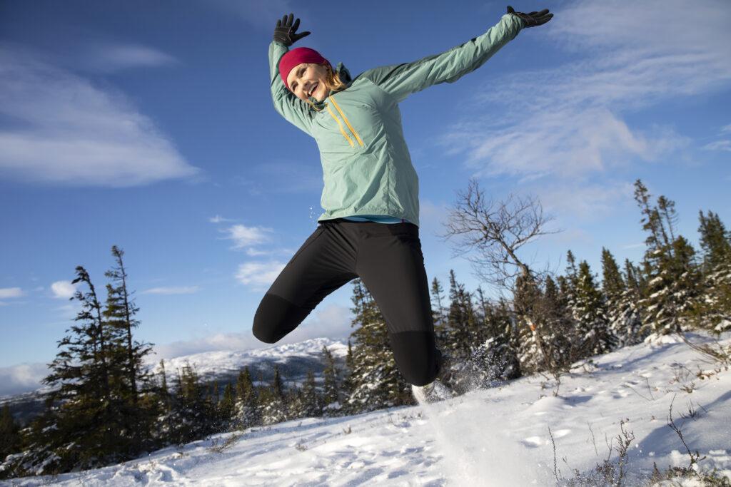 Person hoppar i snön framför Åreskutan. Foto: Susanne Kvarnlöf