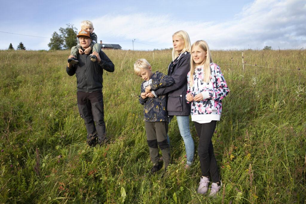 Familj som står på en äng och blickar ut mot fjällen. Foto: Susanne Kvarnlöf