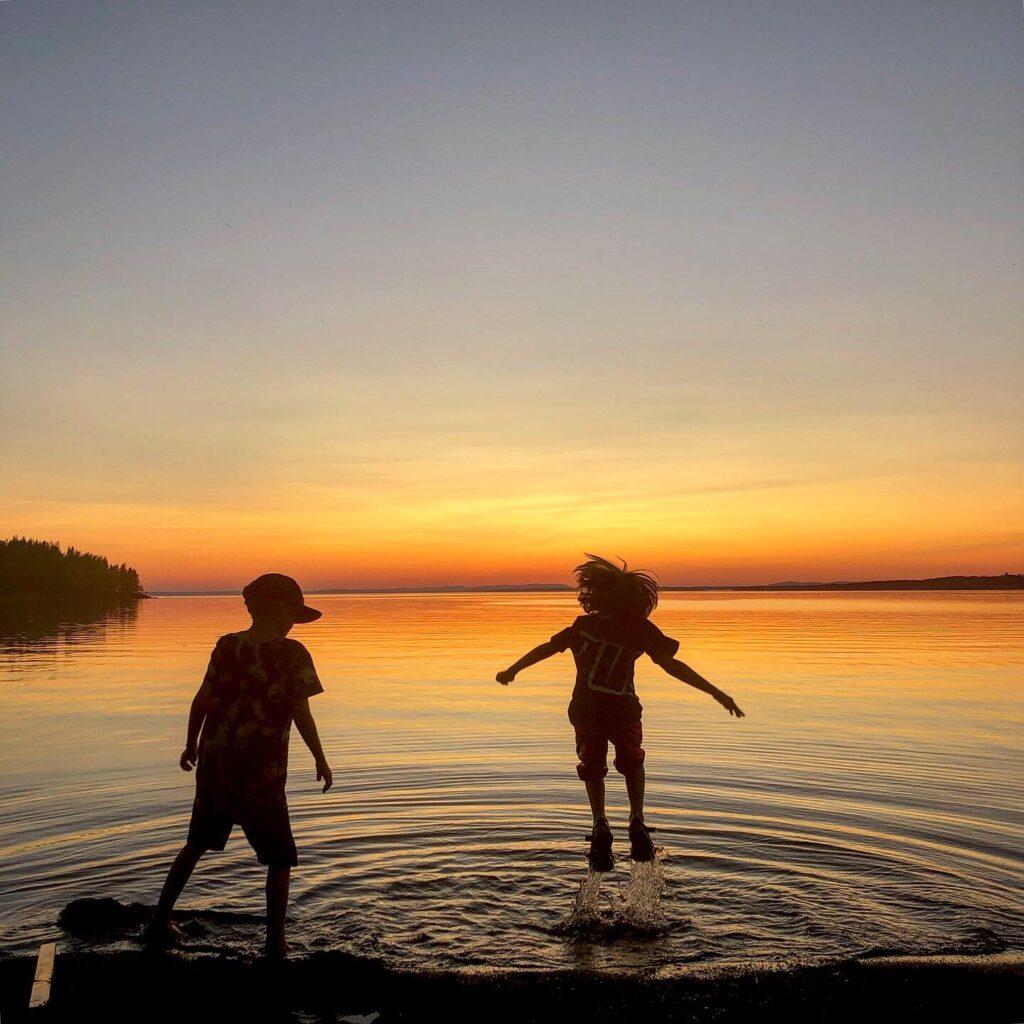 Två barn leker i sjön under solnedgången