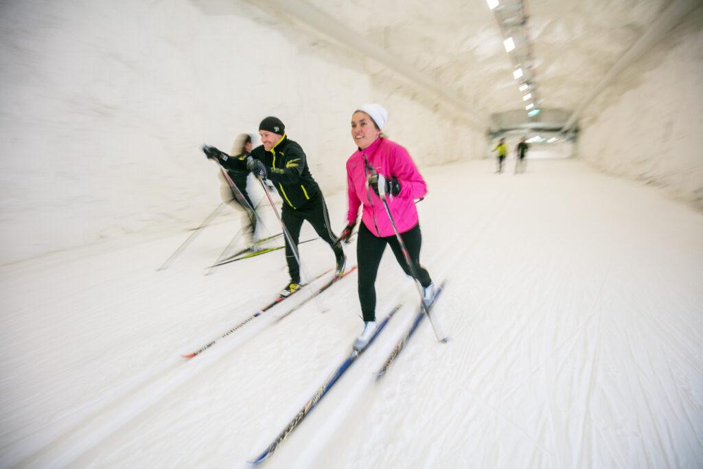 Flera personer åker längdskidor i en skidtunnel