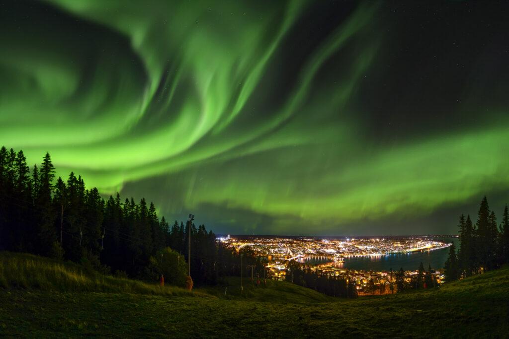 Översikt över staden Östersund med norrsken på himlen