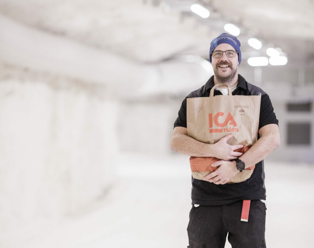 En person håller en ica-kasse framför sig i en skidtunnel