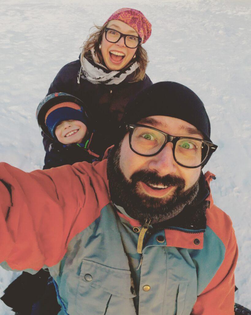 Tre personer tittar in i kameran från en pulkabacke
