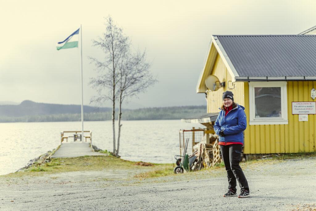 En kvinna står utanför sin fiske camp