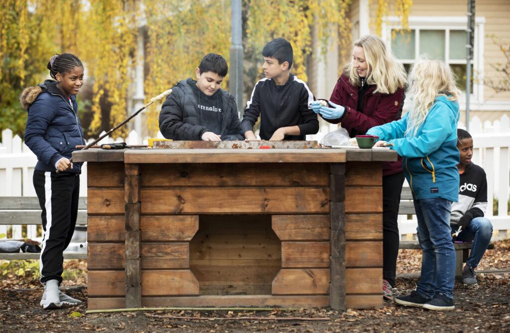 Fyra elever står med sin lärare vid en grillplats