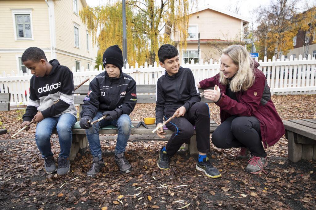 En lärare sitter bredvid tre elever som täljer grillpinnar