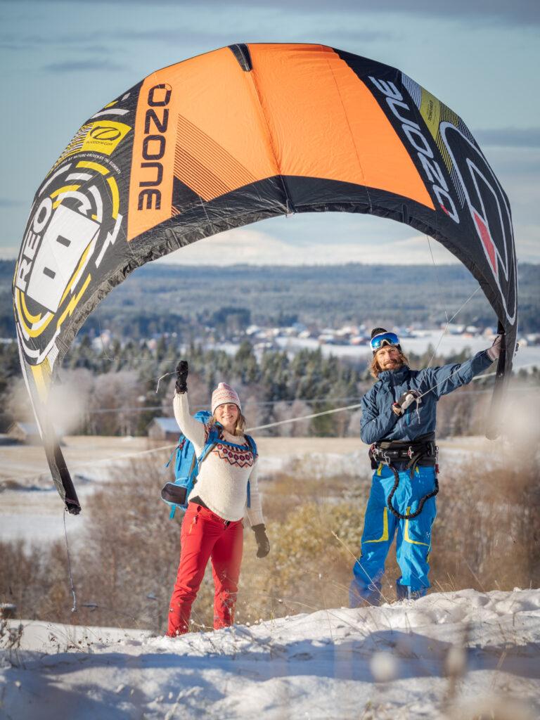 Två personer håller en kite i vinden