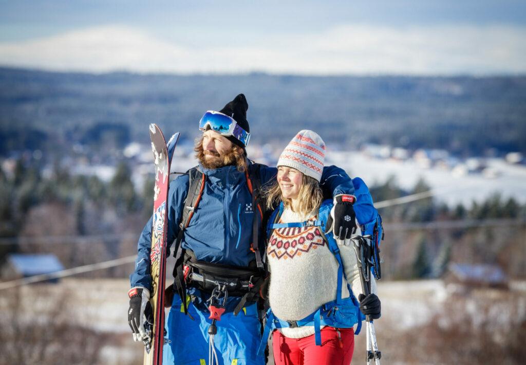 Två personer som står framför ett fjäll och håller i skidor