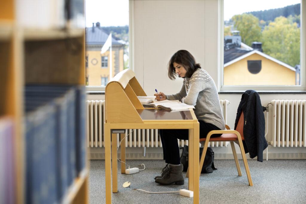 En student pluggar i biblioteket