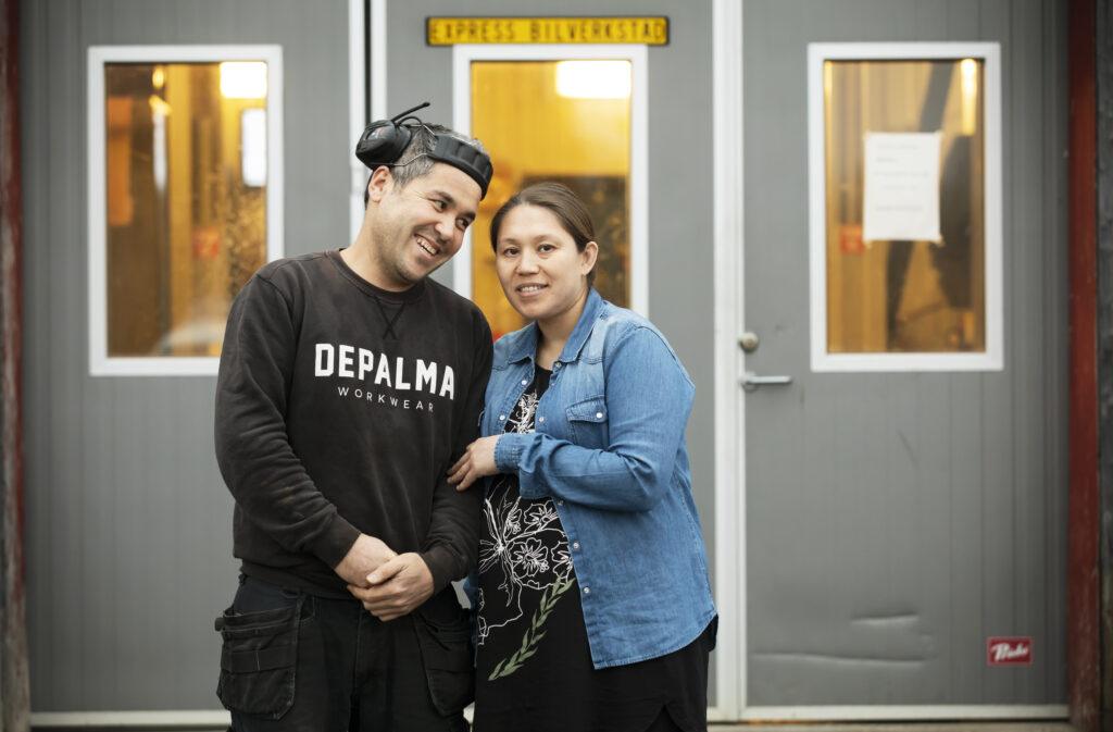 Två personer står framför en bilverkstad
