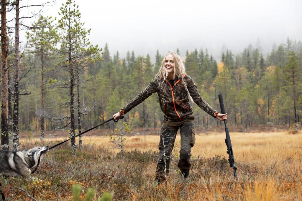 En kvinna står på en myr och håller i en jakthund som drar i kopplet