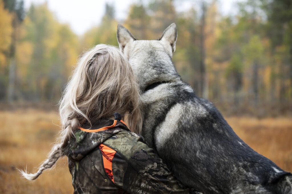 En kvinna och en hund tittar ut mot myren