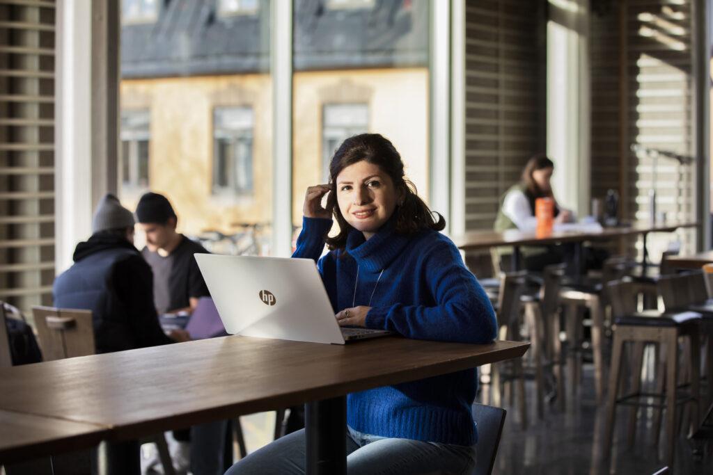 En student pluggar i ett café på ett universitet