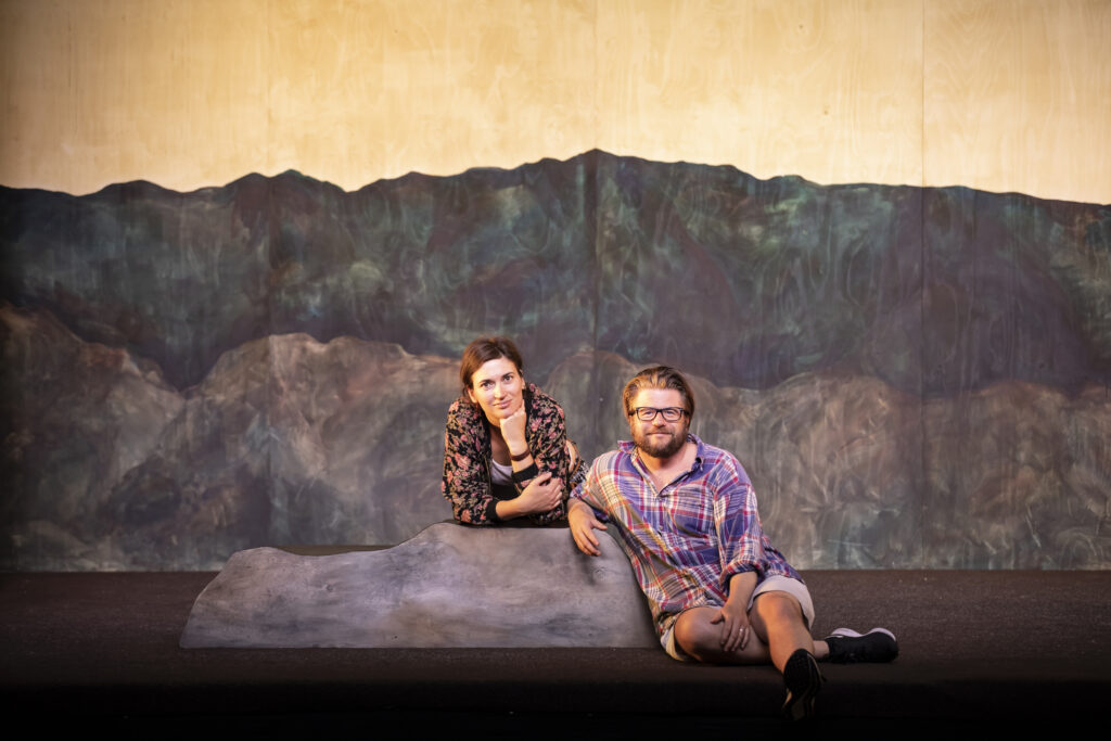 Två personer sitter på en scen som är uppbygd med berg i bakgrunden